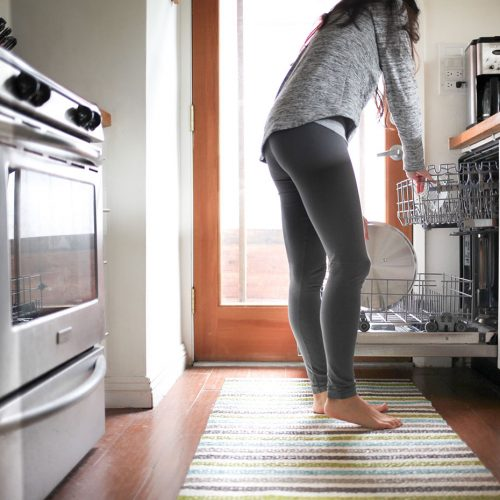 Woman stacking dishwasher in kitchen and making